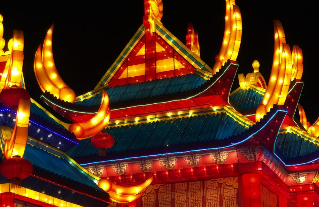 An Asian building lights up the night sky. withs its glowing yellow, green and red lights.
