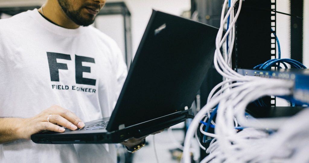 Serious ethnic field engineer examining hardware and working on laptop