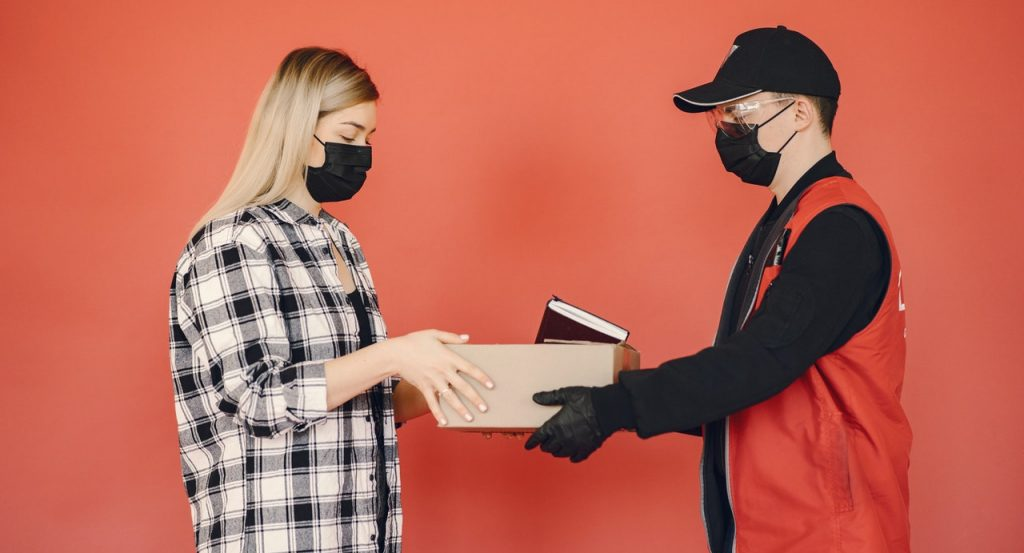 Young female customer receiving order during COVID19 pandemic