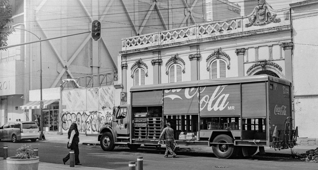 Grayscale Photo of Woman Crossing the Road next to the coca cola old van