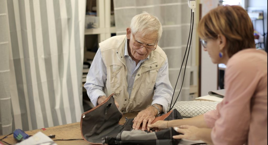 Senior male artisan creating bag together with female assistant