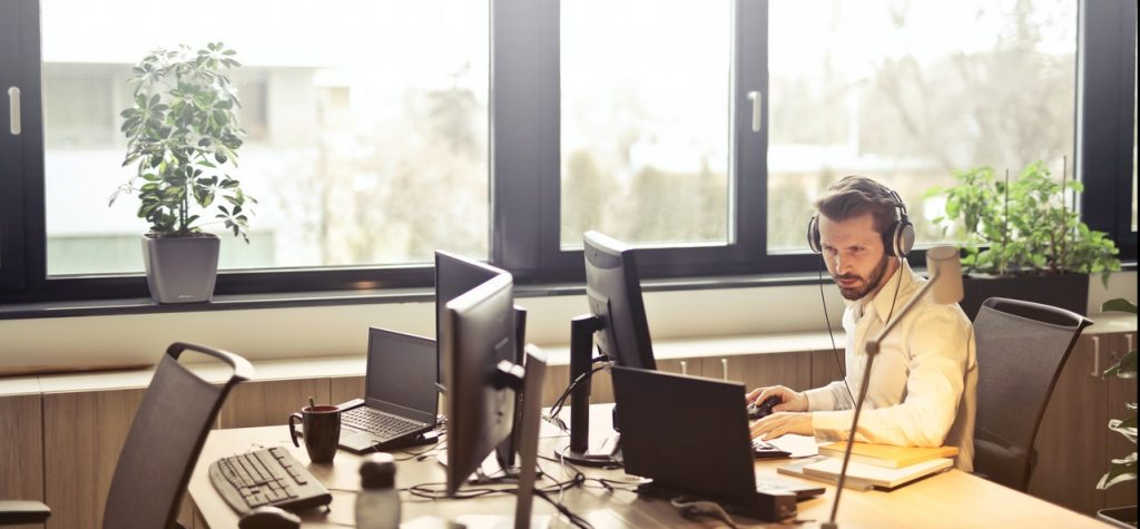 Man With Headphones Facing Computer Monitor