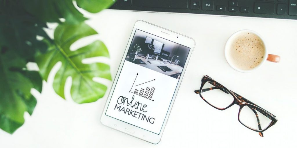 online marketing graphic on screen and brown-rimmed glasses lie on the desk next to the smartphone