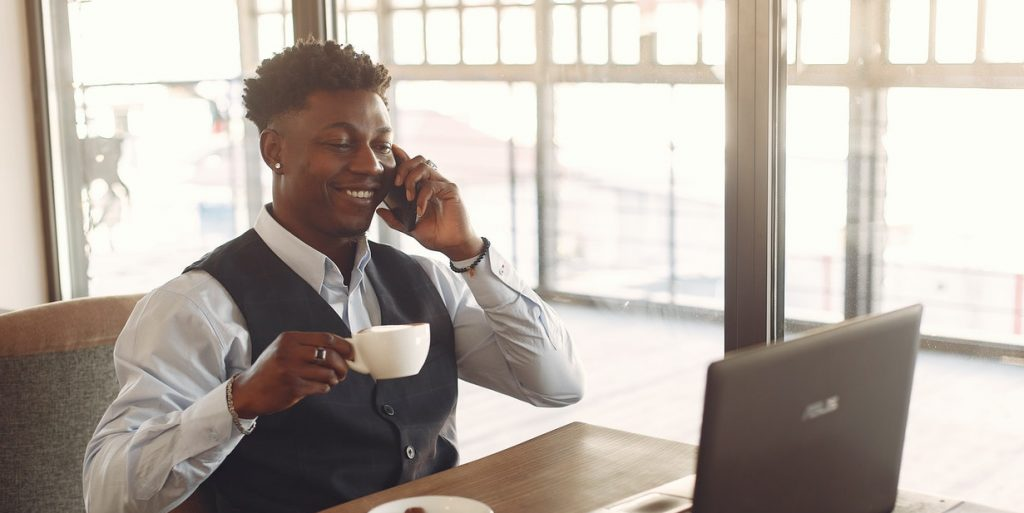 Man Drinking Coffee While Talking On The Phone