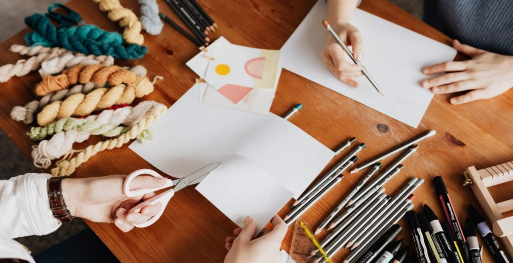 Photo of Two Persons Drawing and Cutting a White Paper