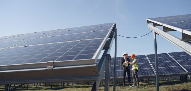 Engineer interacting with colleague standing near solar panels in countryside